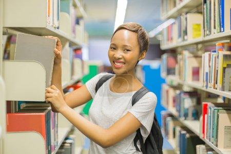 Photo pour Jolie africaine collège fille dans école bibliothèque - image libre de droit