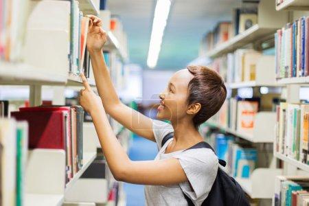Photo pour Portrait d'un étudiant africain à la recherche d'un livre à la bibliothèque - image libre de droit