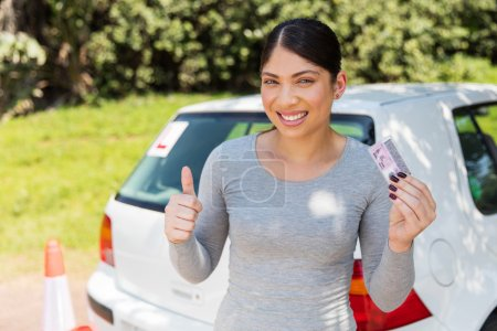 Photo for Excited young woman showing driving license - Royalty Free Image