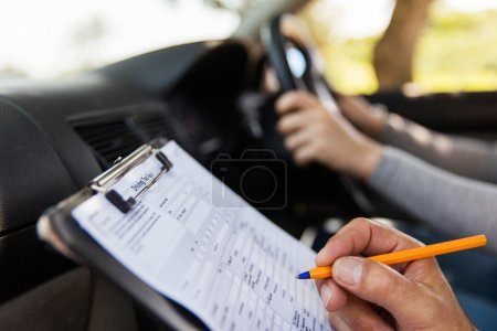 Photo for Student driver taking driving test, closeup of hand writing on clipboard - Royalty Free Image