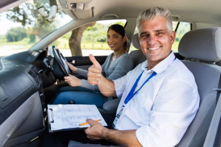 Photo for Smiling senior male driving instructor in car with learner driver giving thumb up - Royalty Free Image