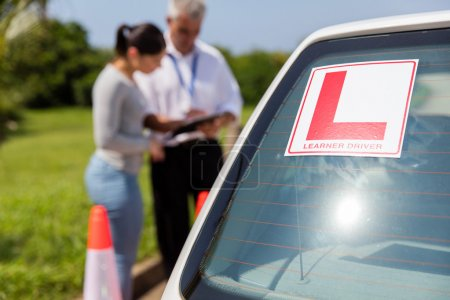 Photo for Female learner driver and instructor behind car outdoors - Royalty Free Image