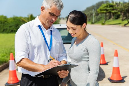 Photo for Happy student driver with senior instructor filling forms before driving test - Royalty Free Image