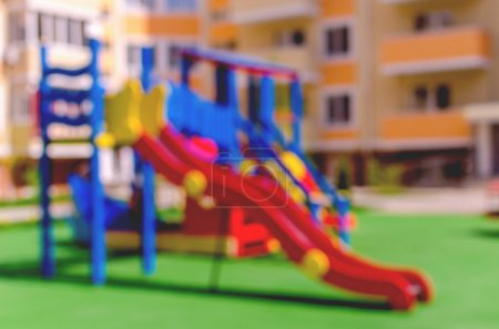 Photo for Defocused and blurred image for background of children's playground. Children's playground in the courtyard of a multistory building in sunny weather - Royalty Free Image