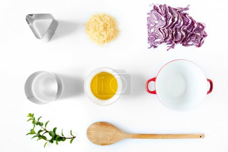 Photo for Composition of ingredients and kitchen utensils used for the preparation of red cabbage risotto. Above view over white background, natural light. - Royalty Free Image