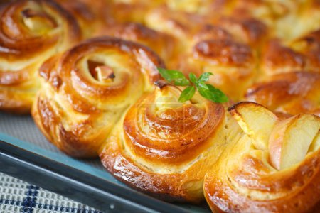 Twisted sweet buns with apple and mint sprig...