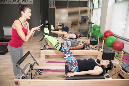 Photo for Exercise on pilates device reformer with instructor at gym - Royalty Free Image