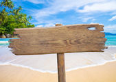 old wooden signboard on tropical beach