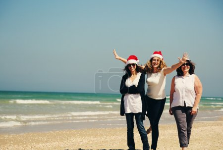 Photo for Three beautiful women wearing christmas hats walking on the seaside - Royalty Free Image