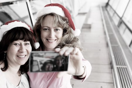 women  in  christmas hats doing selfie