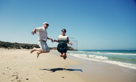 Photo pour Couple de personnes âgées marchant sur la plage - image libre de droit