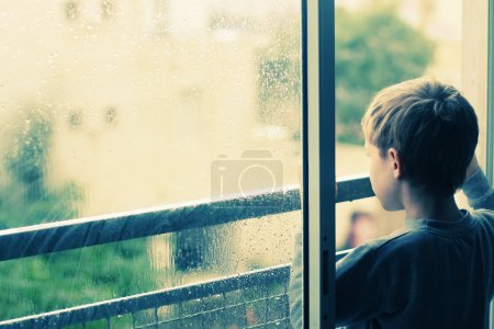 Photo pour Garçon de 6 ans mignon en regardant la pluie - image libre de droit