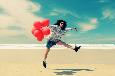 Woman holding red balloons