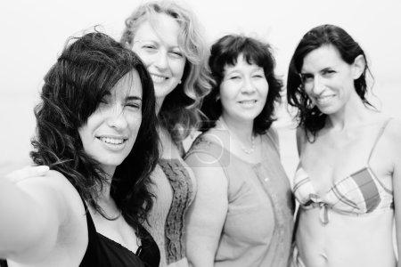 Photo pour Quatre meilleures copines marchant au bord de la mer et faisant selfie-photo au bord de la mer, noir et blanc - image libre de droit
