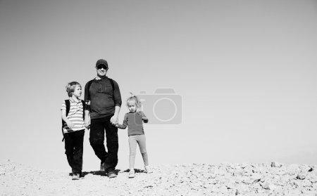 Photo pour Père voyageant avec deux enfants dans le désert - image libre de droit