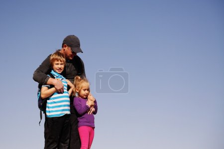 father standing with two kids