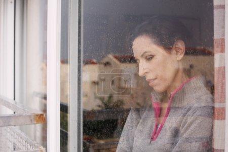 Photo pour Belle femme regardant par la fenêtre - image libre de droit