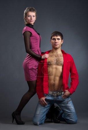 Photo pour Jeune homme et jolie fille posant sur un fond gris - image libre de droit