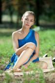 Dívka v modrých šatech pózuje