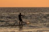 Man paddleboarding silhouette
