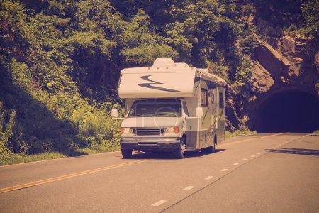 Foto de Imagen de estilo retro filtro de campista Rv conduciendo por autopista con el túnel de roca - Imagen libre de derechos