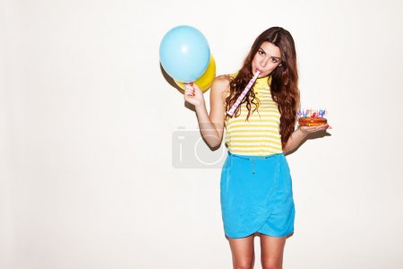 Photo for Pretty birthday girl with ballons and cake blowing the trumpet - Royalty Free Image