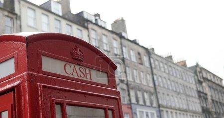 """Photo pour Haut de la cabine téléphonique britannique avec écriture """"cash"""" à Édimbourg, en Écosse - image libre de droit"""