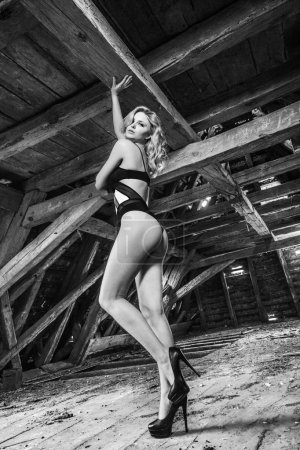 Bottom view of blonde sensual woman posing in old wooden attic of abandoned building wearing black sexy lingerie with smoke under roof - black and white photography