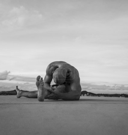 Black and white photo of handsome young man with naked torso doing stretching exercises on a rooftop over sky background