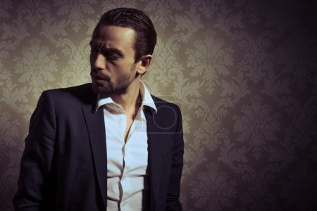Photo for Young handsome and elegant man posing isolated over vintage background - Royalty Free Image