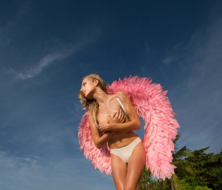 Romantic young beauty as an angel on the tropical beach. Bottom view of blonde pretty topless female woman wearing pink wings and bikini bottom looking somewhere over blue sky and green palm trees background