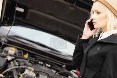 Photo pour Jolie femme blonde jeune branchée assistance routière réclame son véhicule après avoir subi une rupture vers le bas, vue de côté de parler sur son mobile - image libre de droit