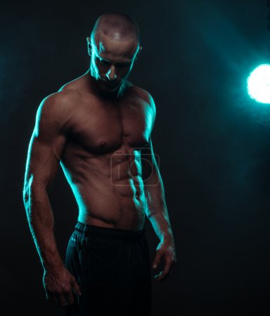 Shirtless Athletic Man Looking Down with Spotlight