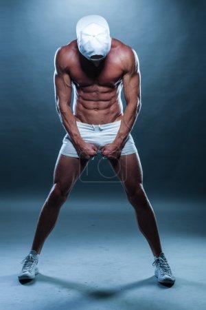 Athletic Man in Mini Shorts and Cap Facing Down