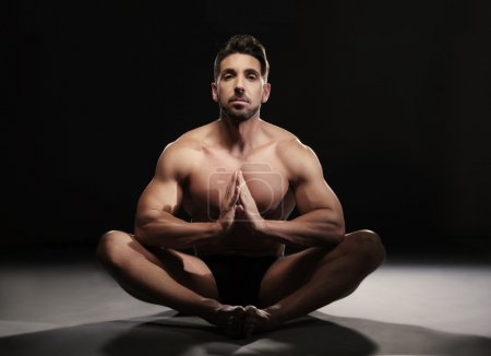 Photo for Portrait of a Topless Muscular Man Sitting on the Floor in a Yoga Position Looking at the Camera on a Black Background. - Royalty Free Image