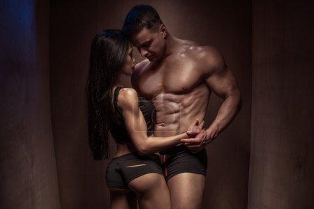Photo pour Portrait d'un couple romantique de jeunes bodybuilding avec des corps sexy posant si fermé contre un fond mural en bois brun - image libre de droit