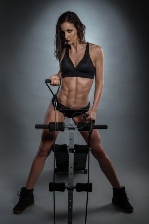 Athletic Sexy Young Woman Posing at Rowing Machine