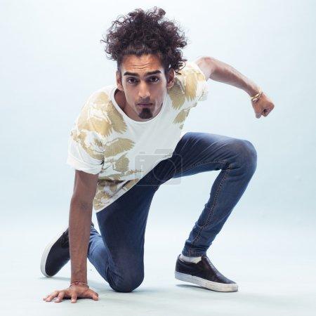 Young Male Hip Hop Dancer Kneeling on the Floor