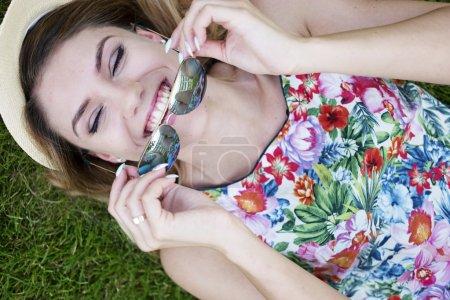 Photo pour Gros plan Angle élevé Vue d'une jolie jeune femme heureuse tenant ses nuances tout en s'allongeant sur les graminées vertes - image libre de droit