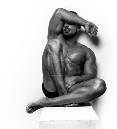 Homme Musclé assis sur blanc