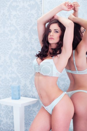 Photo for Sexy brunette woman in lingerie posing in bedroom against the mirror - Royalty Free Image