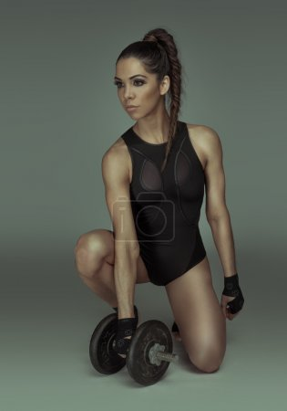 Photo for Determined fit sexy woman working out with dumbells wearing gloves and body - Royalty Free Image