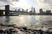 Manhattan skyline and Brooklyn bridge. East river waves. New York City. United States of America.