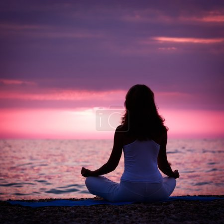 Woman Meditating in Lotus Position by the Sea