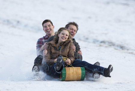 Photo pour Heureuse famille adulte profitant d'un plaisir d'hiver sur un toboggan . - image libre de droit