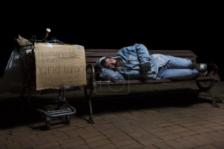 Photo for Homeless man at night sleeping on a park bench with his shopping cart full of his possessions - Royalty Free Image