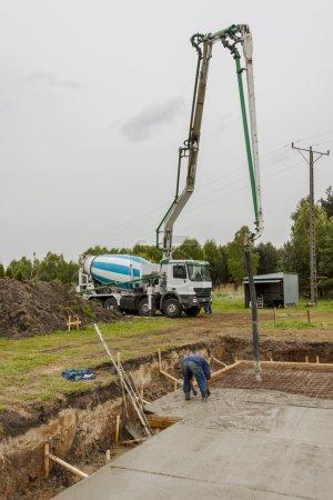 Worker pouring concrete mix.