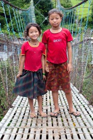 Little Nepalese girls on rope hunging suspension bridge