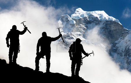 Silhouette of men with ice axe in hand and mountains