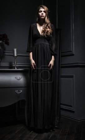 Photo for Sexy young woman in black dress standing on background of vintage dark interior - Royalty Free Image